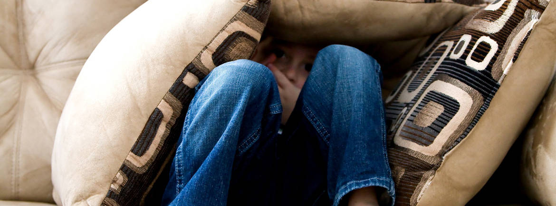 Angstig jongetje verstopt zich tussen kussens